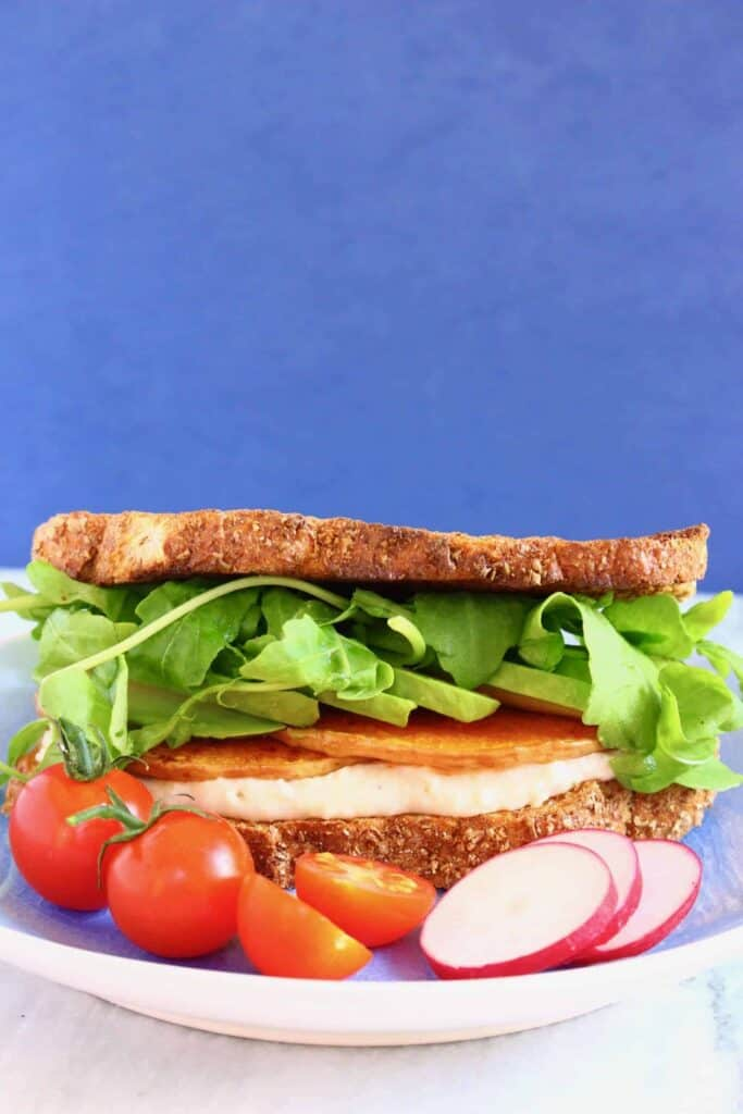 A sandwich with roasted butternut squash slices, white hummus, sliced hummus and rocket against a blue background