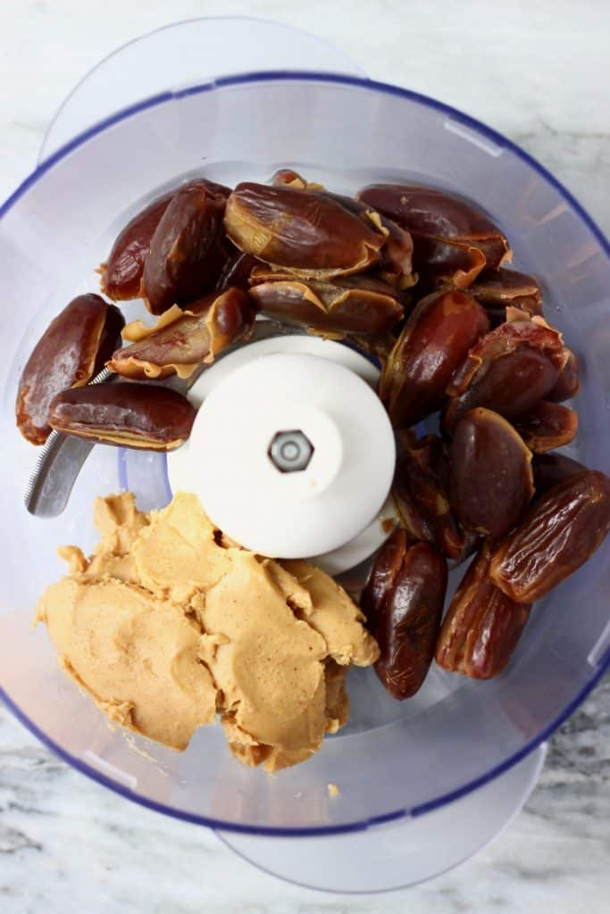 Dates, almond butter and salt in a food processor against a marble background