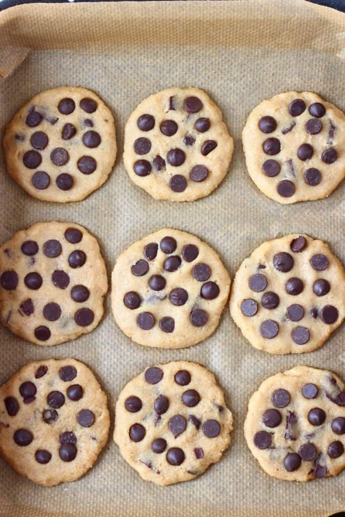 Nine raw chocolate chip cookies on a baking tray lined with brown baking paper