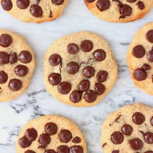 Six chocolate chip cookies against a marble background