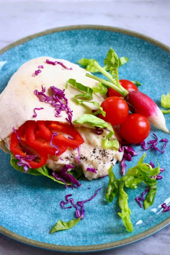 Half a white pitta bread filled with creamy white beans, lettuce and sliced red pepper on a blue plate