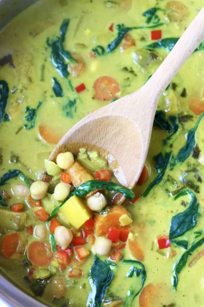 Yellow curry made using diced mango, chickpeas, carrots and spinach in a silver pan being stirred with a wooden spoon