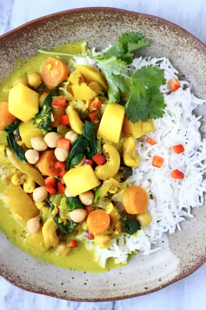 Curry made with mango, cashew nuts, spinach and chickpeas with white rice on a brown plate against a marble background