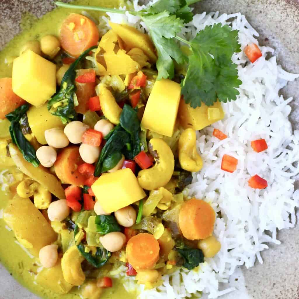 Curry made with mango, cashew nuts, spinach and chickpeas with white rice on a brown plate