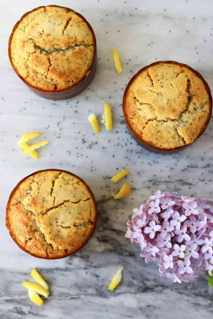 Three lemon poppy seed muffins in brown muffin cases with bits of lemon zest and a lilac flower scattered on a marble background