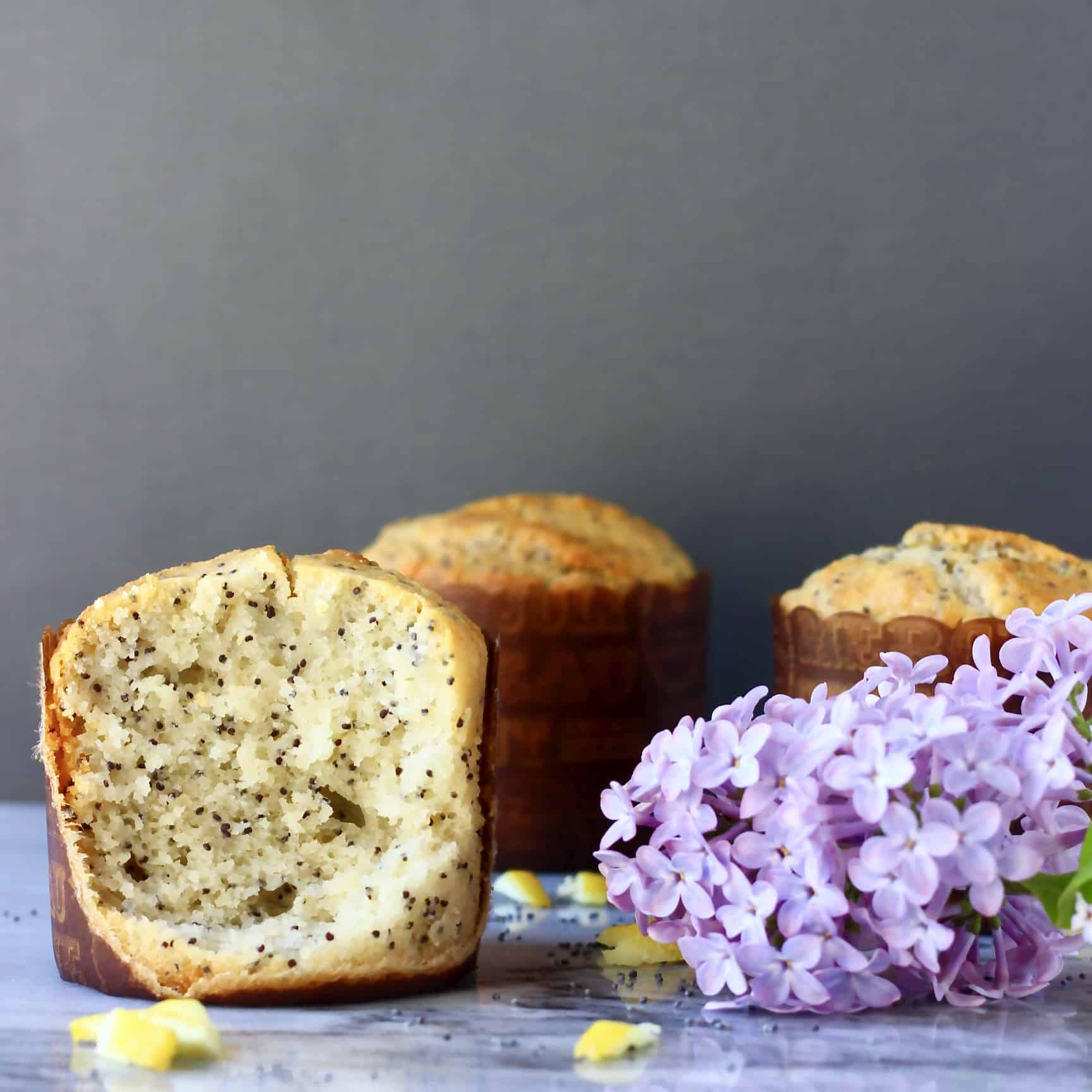 Three lemon poppy seed muffins with a lilac flower on a marble slab against a grey background