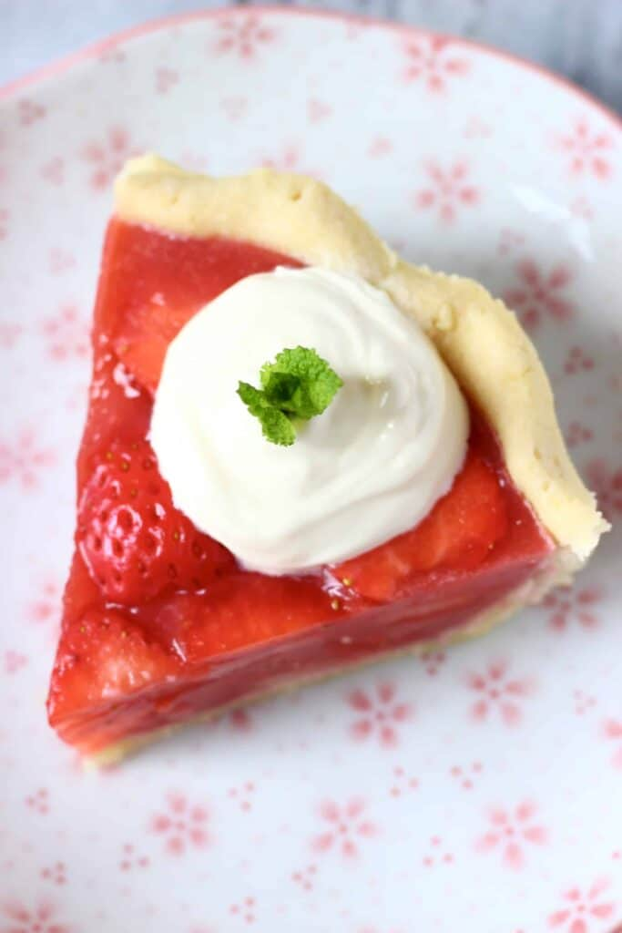 Photo of a slice of strawberry pie topped with cream and a sprig of mint against a white plate with pink flowers