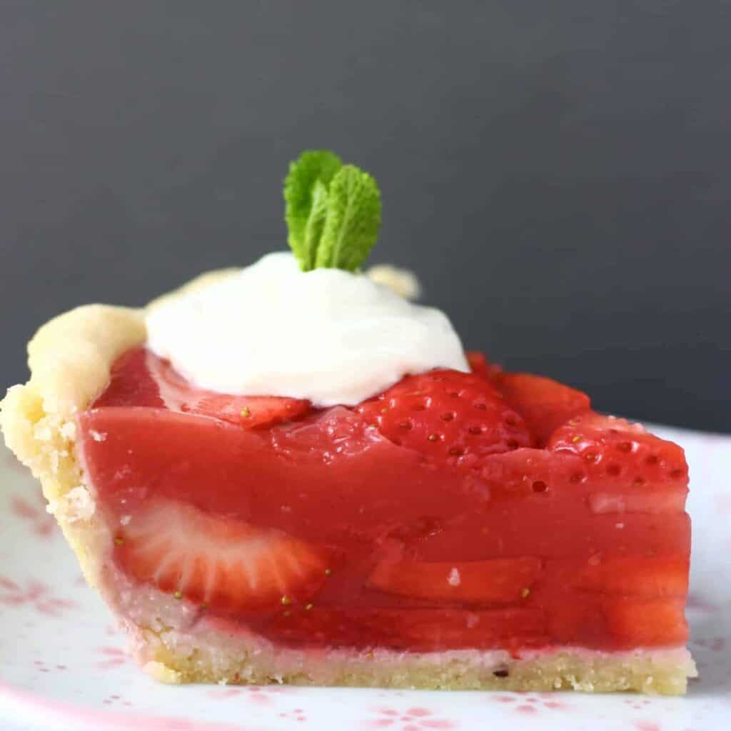 Photo of a slice of strawberry pie topped with whipped cream and a sprig of mint on a pink plate against a grey background