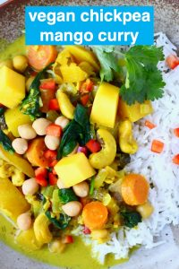 Chickpea, mango and vegetable curry with white rice on a brown plate