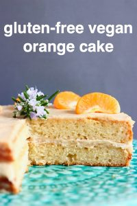 A sliced orange sponge cake with white buttercream frosting topped with clementine slices on a green cake stand against a grey background