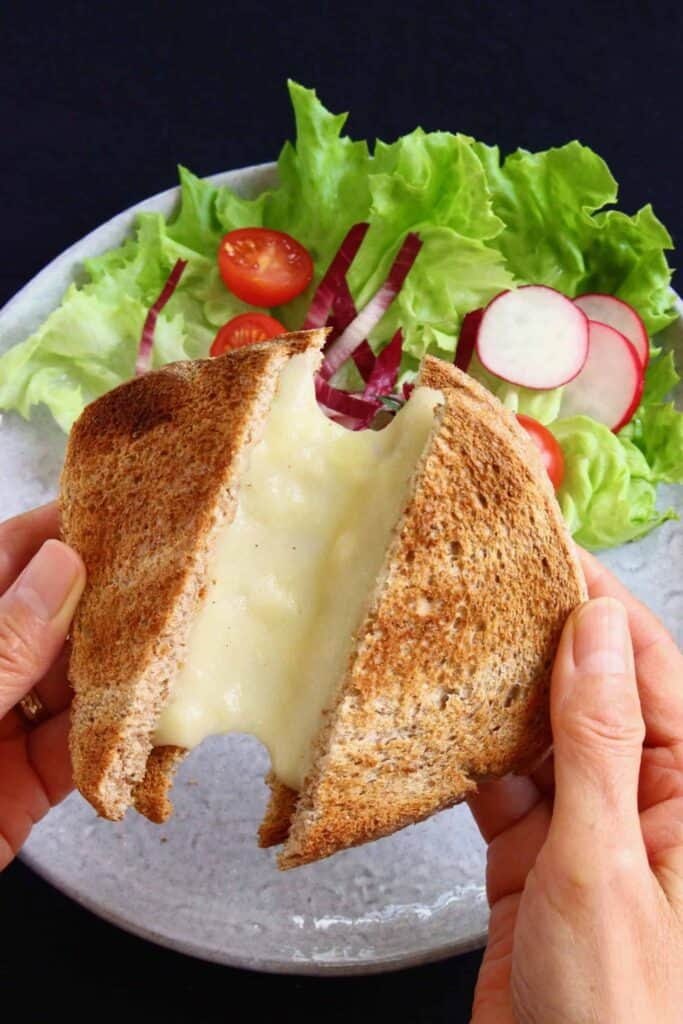 A toasted grilled cheese sandwich being pulled apart by two hands against a grey plate with lettuce