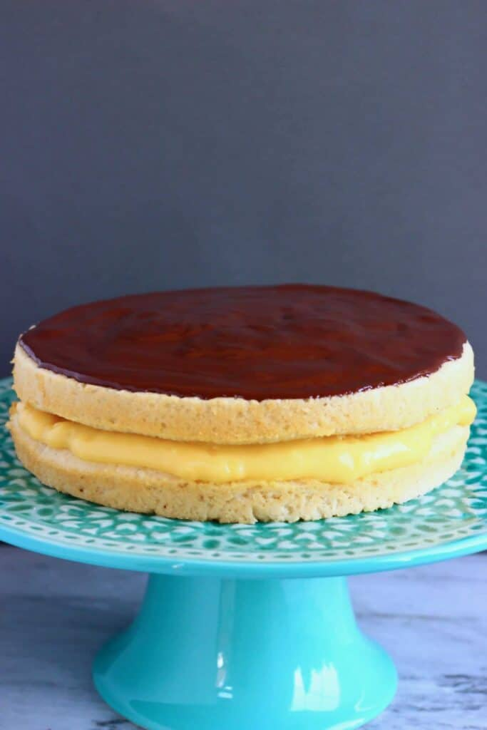 A golden brown sponge cake filled with yellow custard topped with chocolate ganache on a green cake stand against a grey background