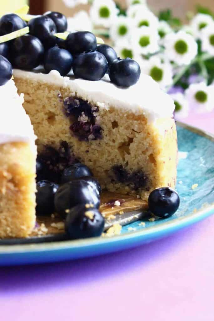 Photo of a sliced sponge cake with blueberries in it topped with white creamy frosting and fresh blueberries on a blue plate against a purple background with small white flowers