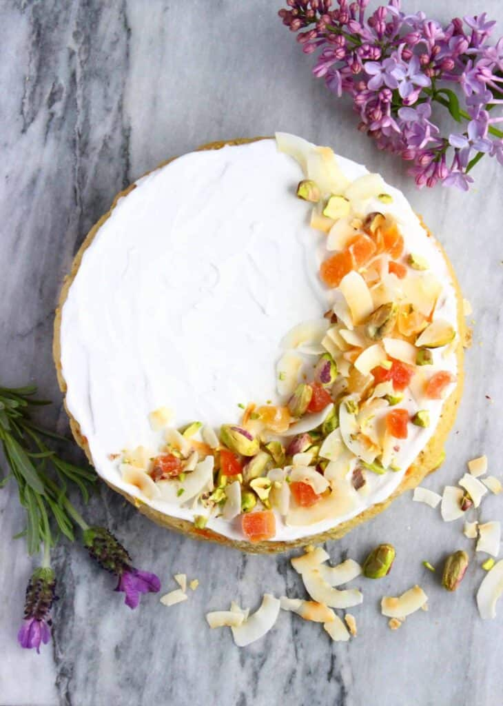 Photo of a sponge cake topped with creamy white frosting, sprinkled with dried mango, pistachio nuts and coconut flakes against a marble background
