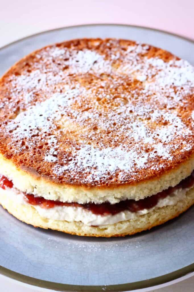Photo of a golden brown sponge cake sandwiched with strawberry jam and white buttercream dusted with icing sugar on a grey plate