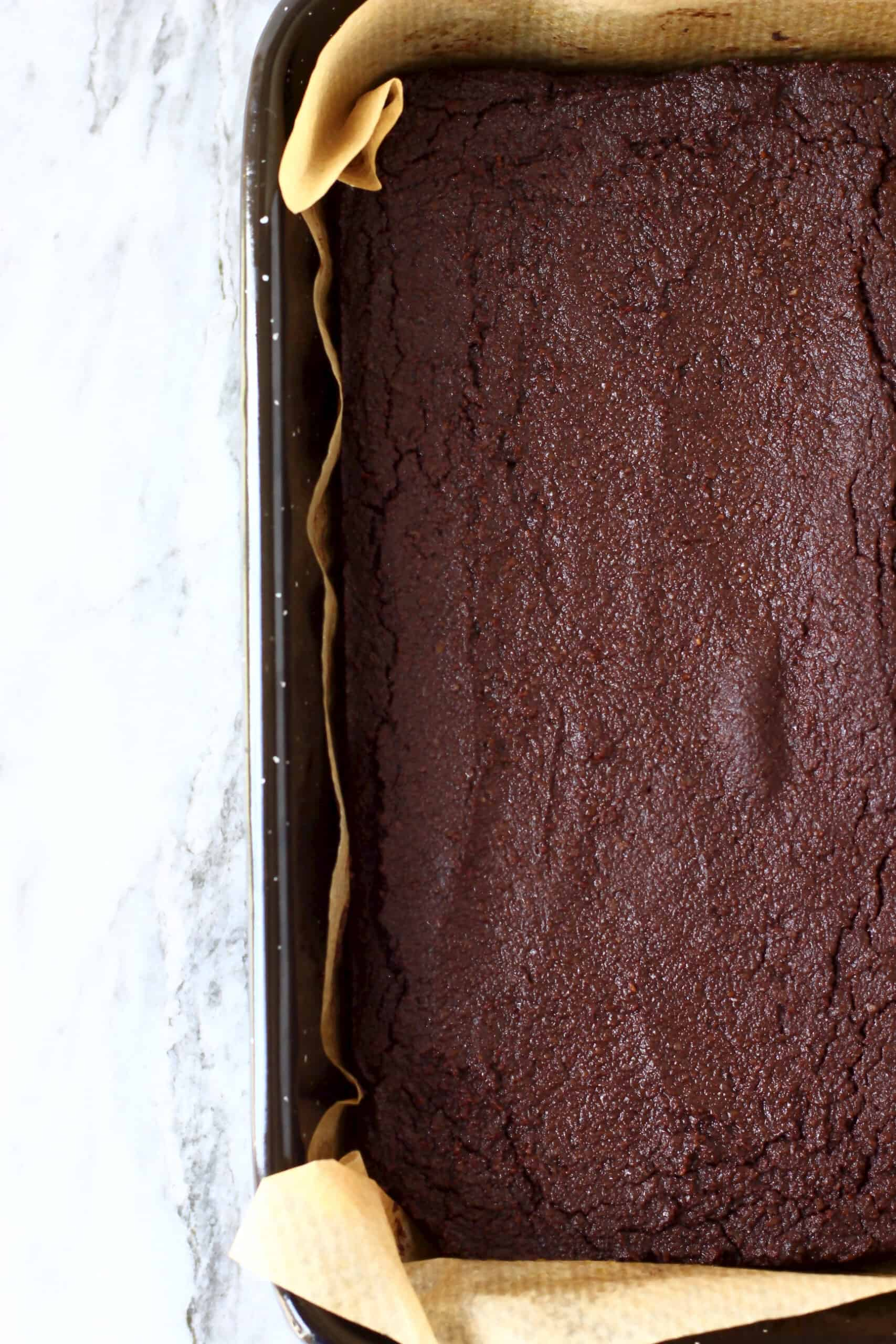 Vegan gluten-free chocolate brownies in a square baking tin lined with baking paper