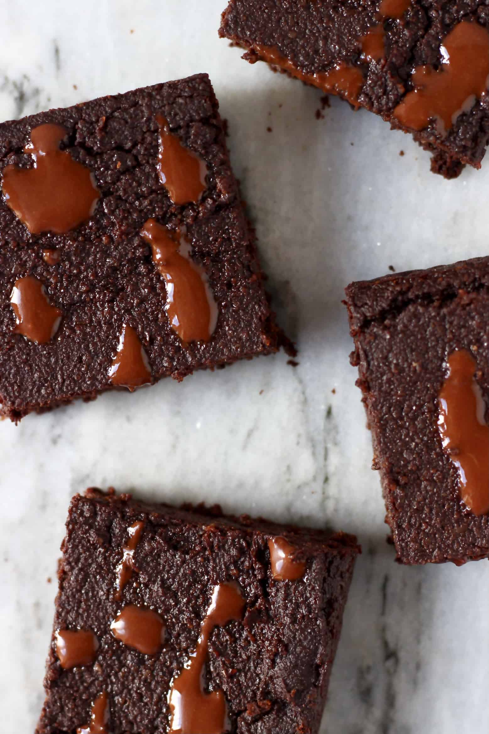 Four square vegan gluten-free chocolate brownies on a marble background