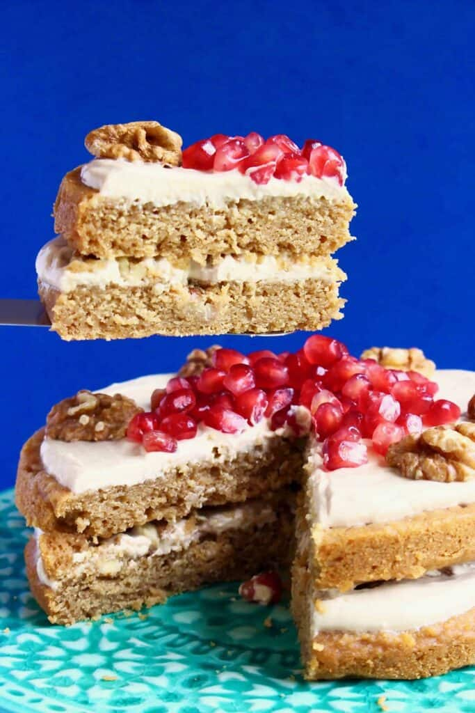 Photo of a coffee cake sandwiched with creamy white frosting and topped with walnuts and pomegranate seeds with one slice being held up in the air against a dark blue background