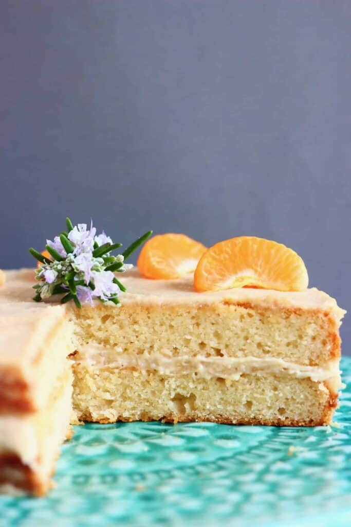 Photo of a sliced orange cake topped with clementine segments and purple rosemary flowers on a green cake stand against a grey background