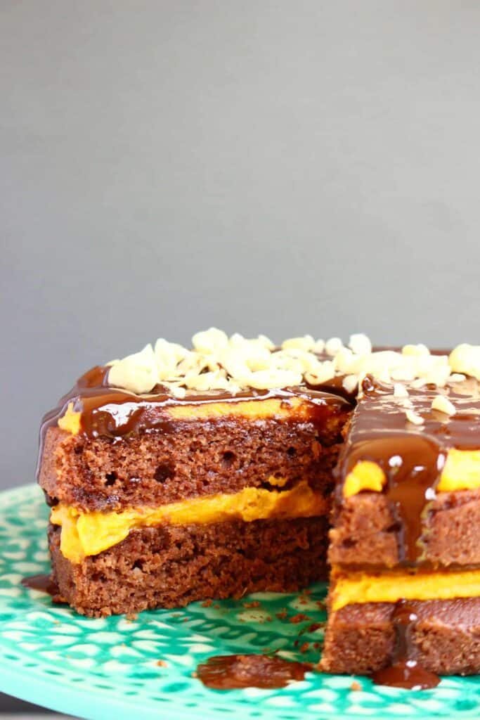 Photo of chocolate cake sandwiched with yellow peanut butter frosting, drizzled with chocolate ganache and sprinkled with chopped peanuts on a green cake stand against a grey background
