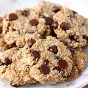 A pile of gluten-free vegan oatmeal chocolate chip cookies on a plate