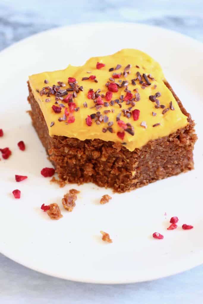 Photo of a square slice of chocolate cake topped with yellow frosting sprinkled with cacao nibs and freeze-dried raspberries on a small white plate against a marble background