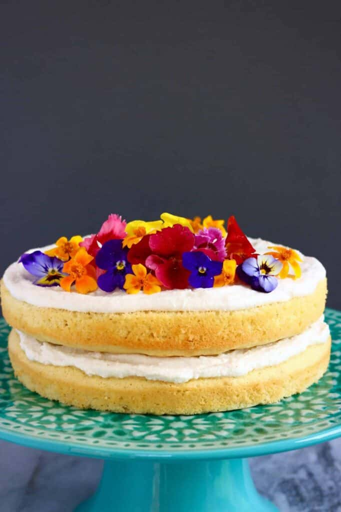 Photo of a yellow sponge cake with white creamy frosting topped with edible flowers on a blue cake stand against a grey background