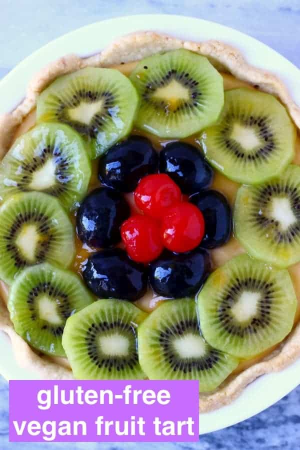 Photo of a fruit tart topped with sliced kiwi, grapes and cherries in a white pie dish against a marble background