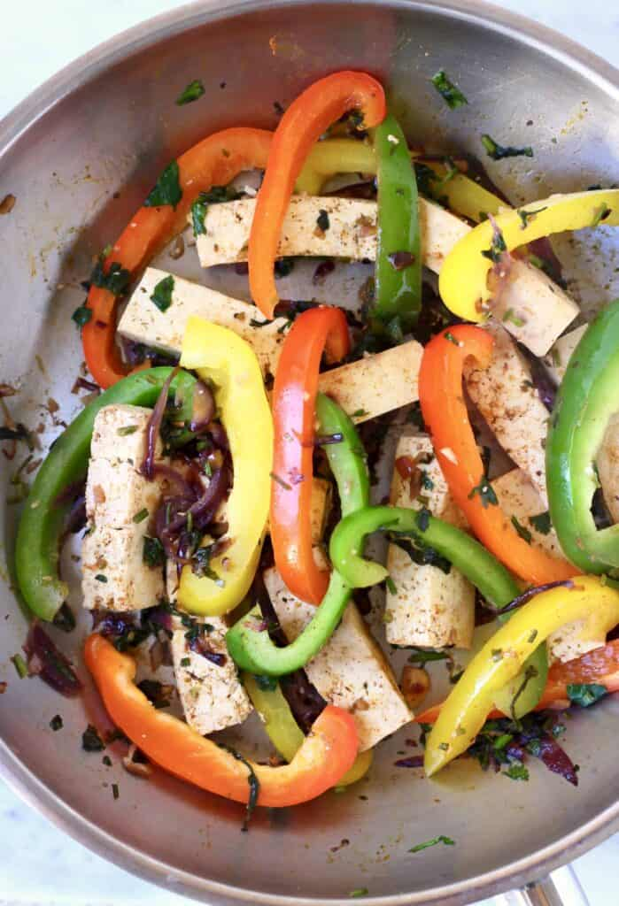 Cubes of tofu and sliced peppers in a silver frying pan with spices and herbs against a marble background