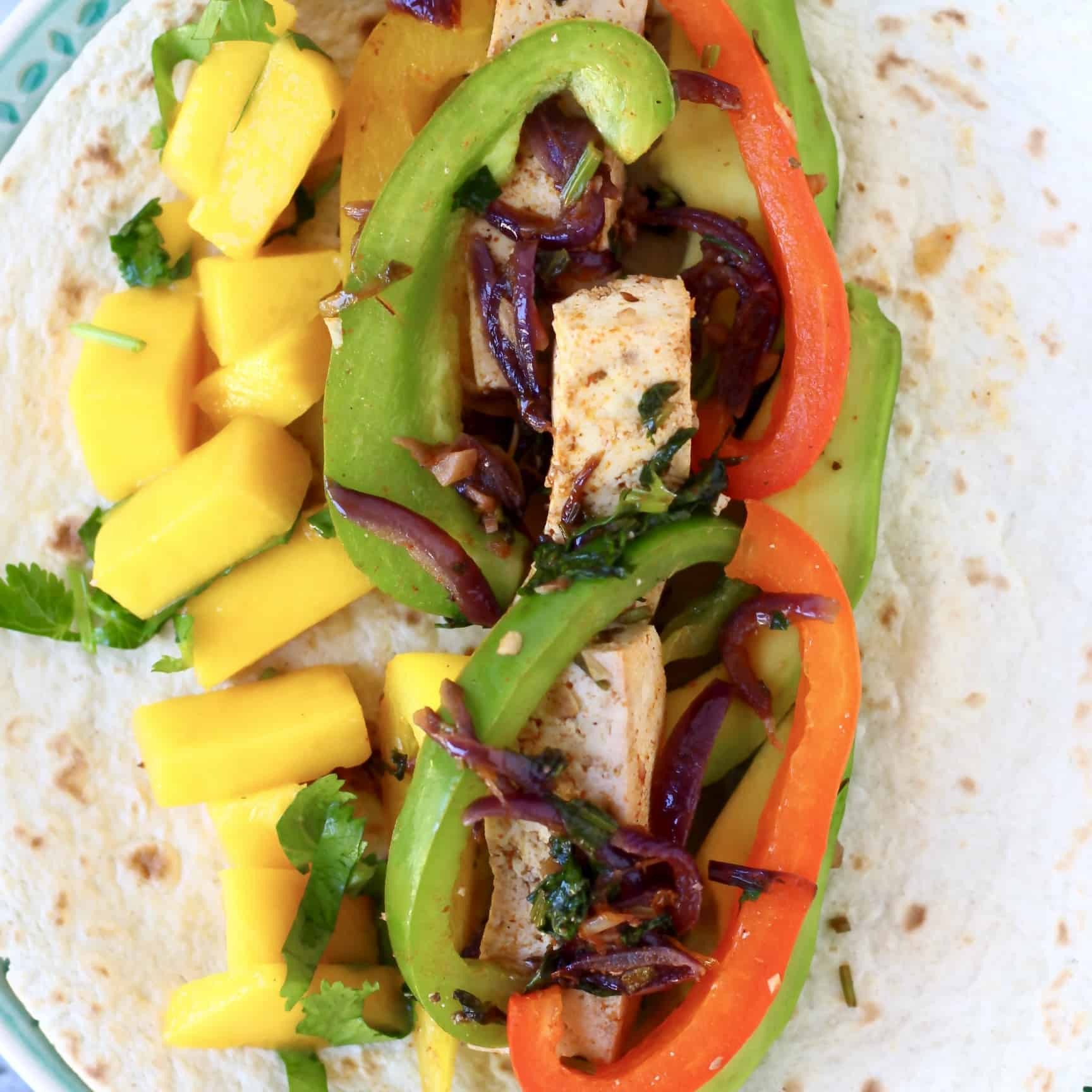 Tofu, sliced peppers and diced mango on a tortilla on a blue plate