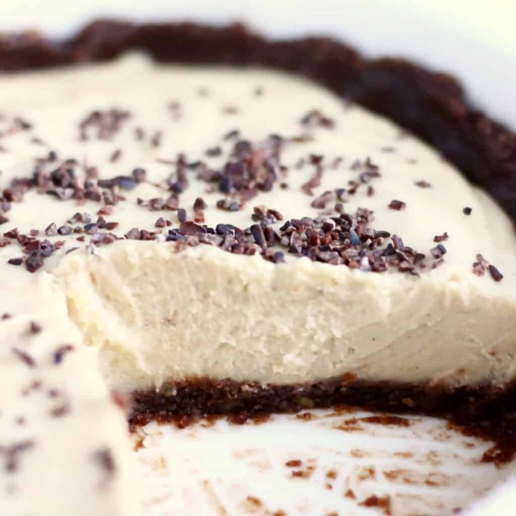 Photo of a sliced pie in a white pie dish - a brown chocolate crust with a light brown filling and sprinkled with cacao nibs