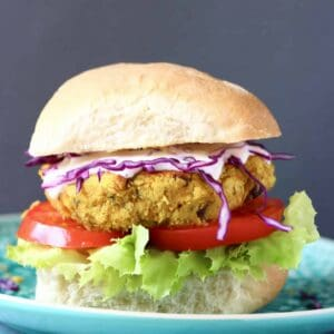 Photo of a curried chickpea burger with a bun, tomato, lettuce and purple cabbage against a grey background