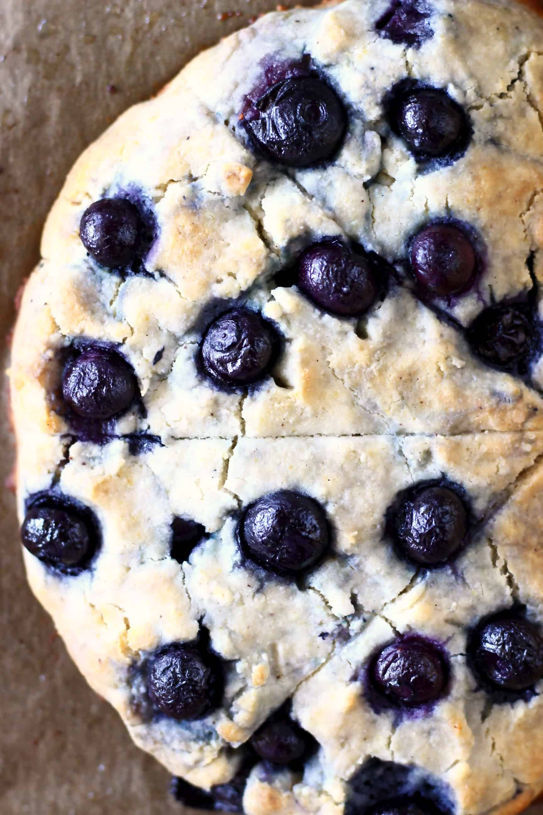 Four triangular gluten-free blueberry scones bunched together on a sheet of brown baking paper