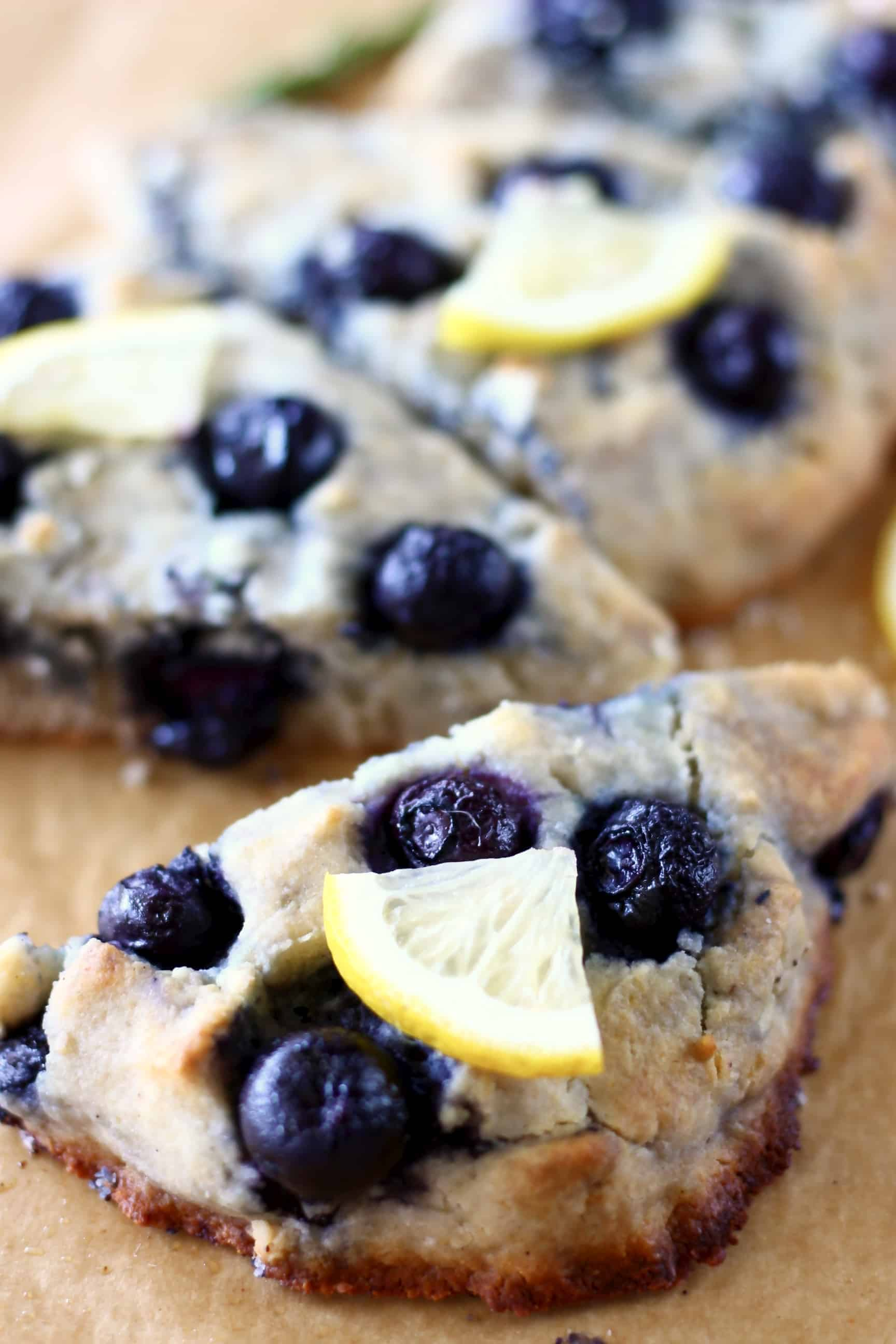 Three gluten-free blueberry scones topped with lemon wedges on a sheet of brown baking paper