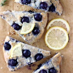 Photo of four triangular blueberry scones topped with lemon wedges on a sheet of brown baking paper