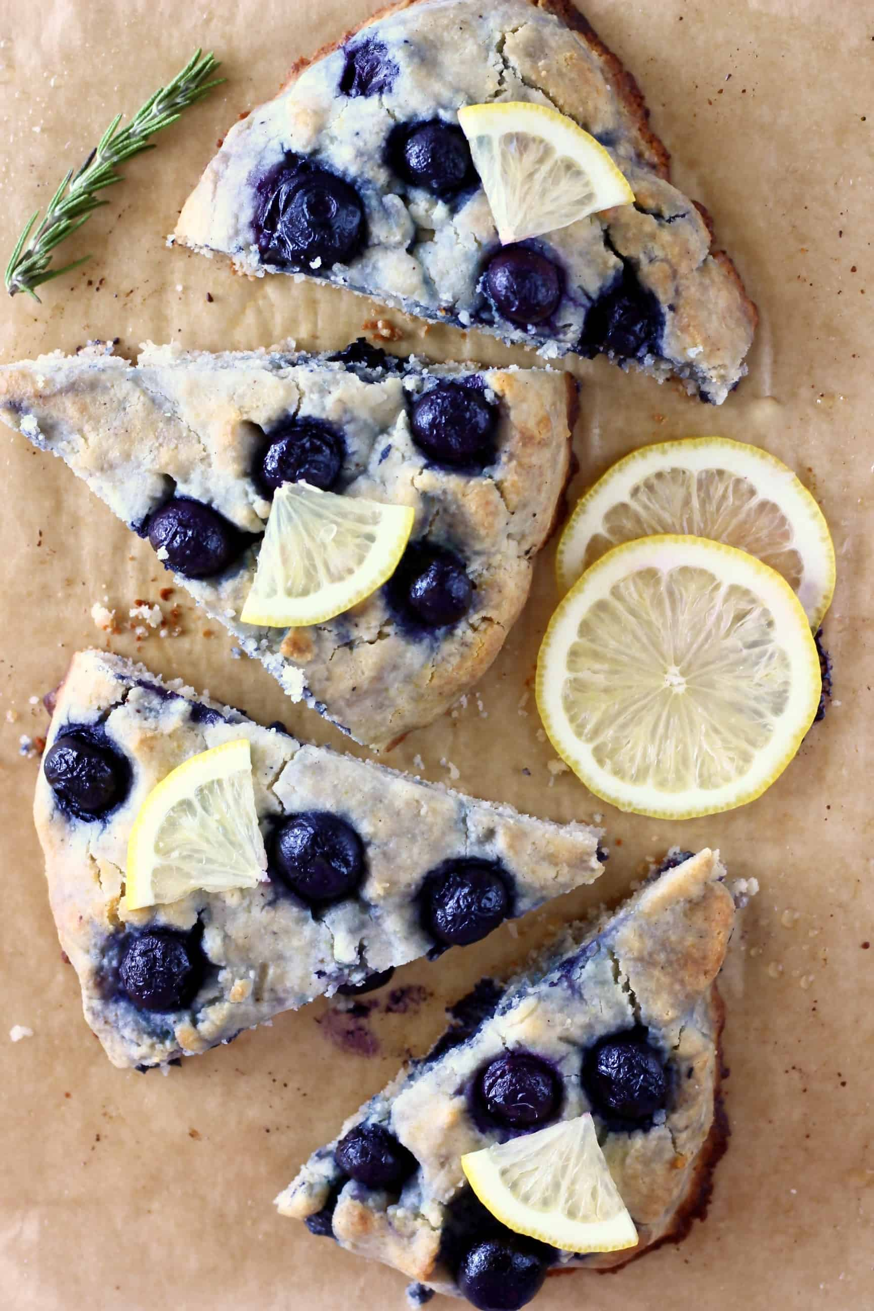 Four triangular gluten-free blueberry scones topped with lemon wedges on a sheet of brown baking paper