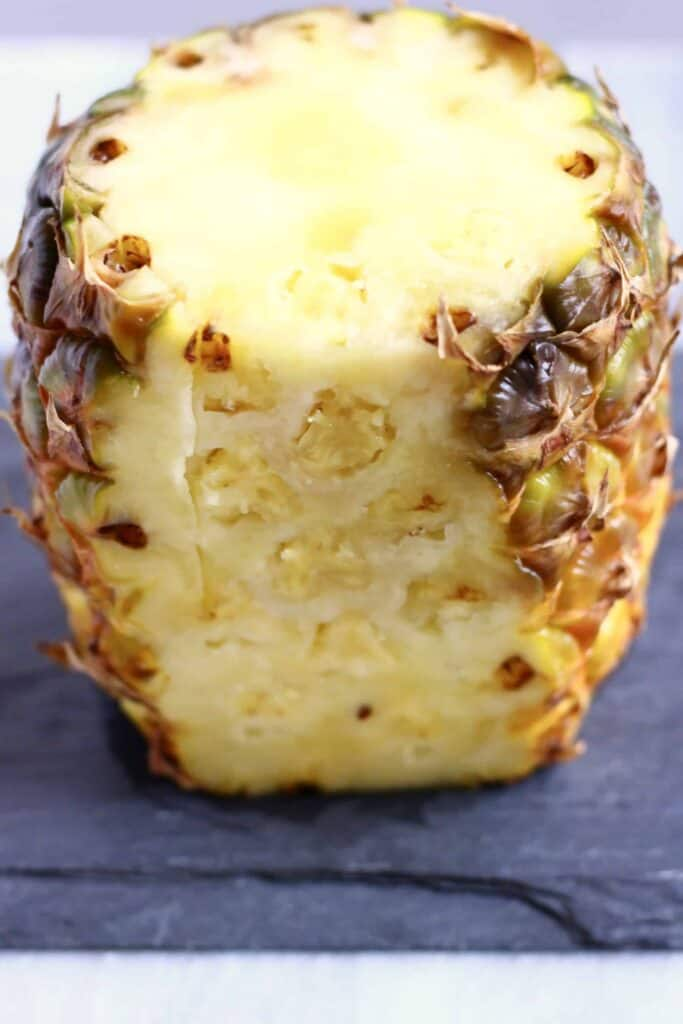 Photo of a vertical pineapple with the top and half of the skin cut off on a black slab