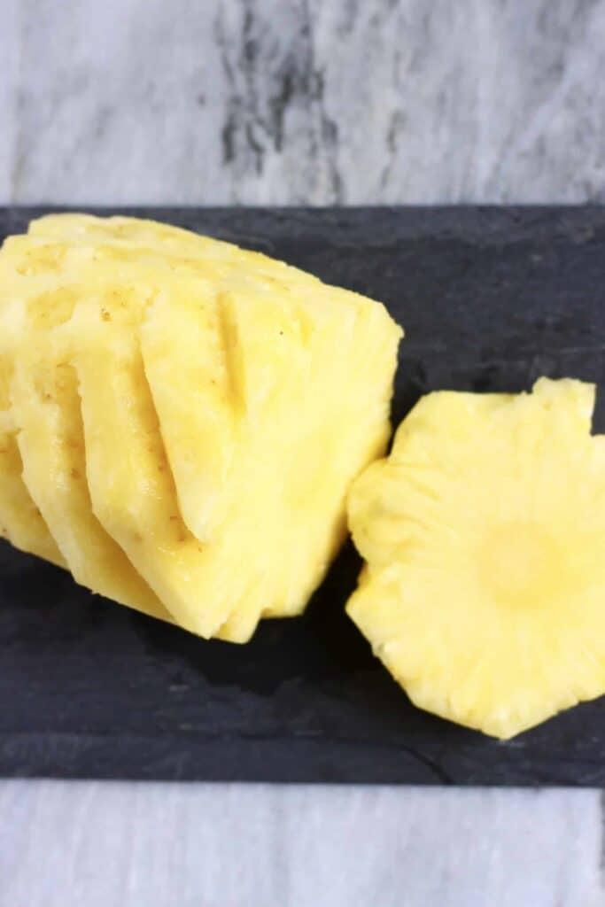 Photo of a sliced pineapple on a black slab against a marble background