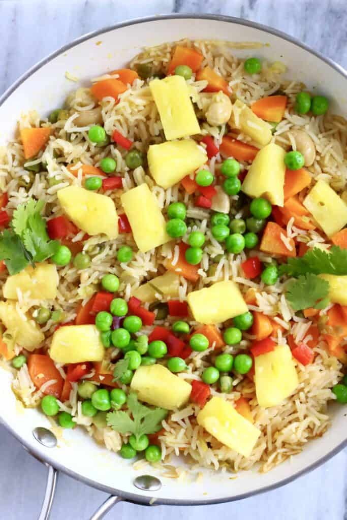Photo of a saucepan with rice, green peas, carrots and pineapple chunks
