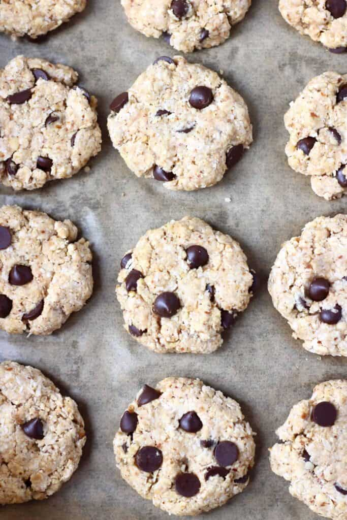 Photo of twelve raw chocolate chip cookies on a piece of brown baking paper