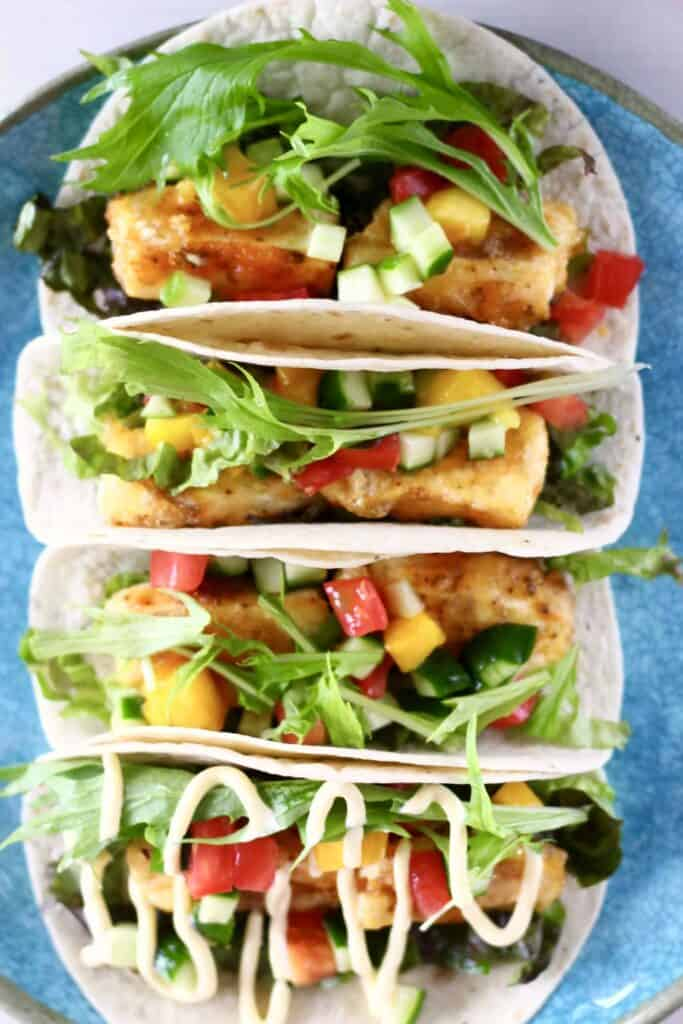 Photo of four tortillas stuffed with crispy tofu, mango, tomato, cucumber and lettuce on a blue plate