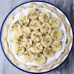 Photo of banana cream pie topped with slices of banana in a blue rimmed pie dish against a marble background
