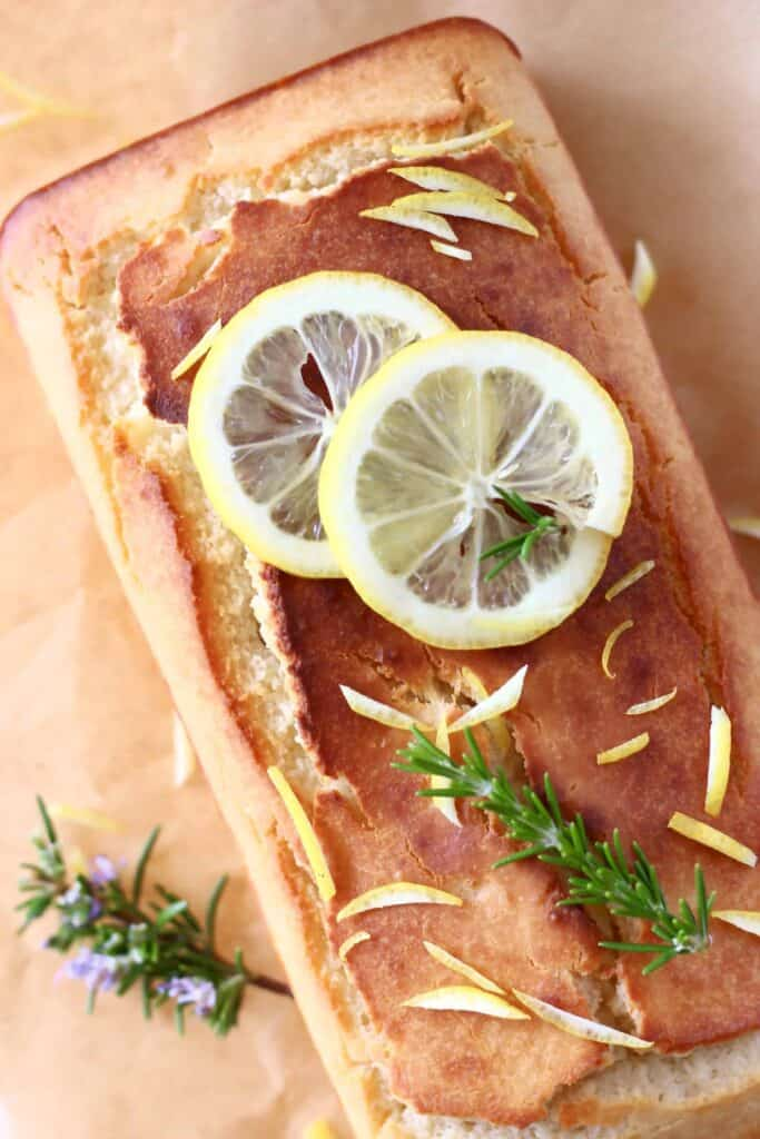 Photo of a golden brown pound cake topped with lemon slices and sprigs of rosemary on top of brown baking paper