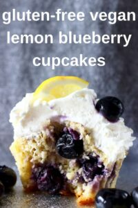 Photo of a blueberry cupcake topped with white creamy frosting and a fresh blueberry and lemon wedge against a grey background