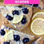 Four triangular blueberry scones topped with lemon wedges on a sheet of brown baking paper