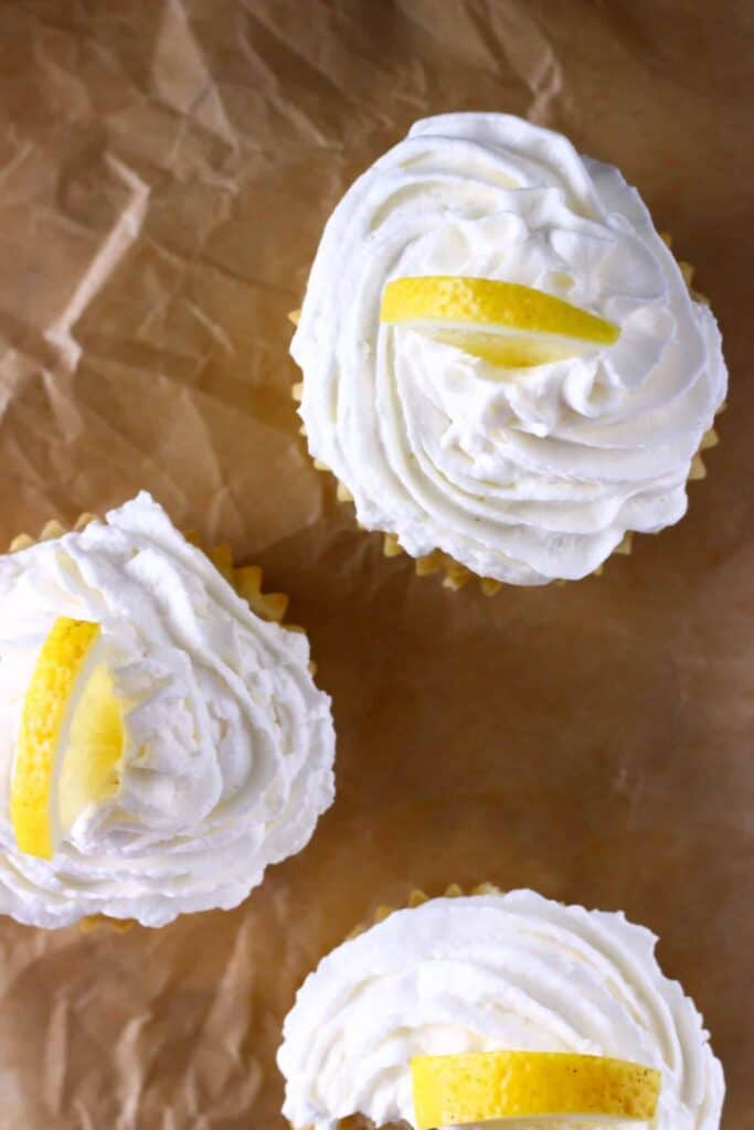 Three lemon cupcakes with frosting shot from above