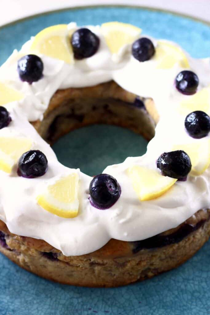 Photo of a bundt cake topped with cream cheese frosting, fresh blueberries and lemon wedges on a big blue plate