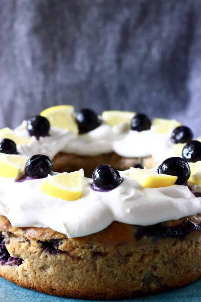 Photo of a bundt cake topped with white frosting, fresh blueberries and lemon wedges against a grey background