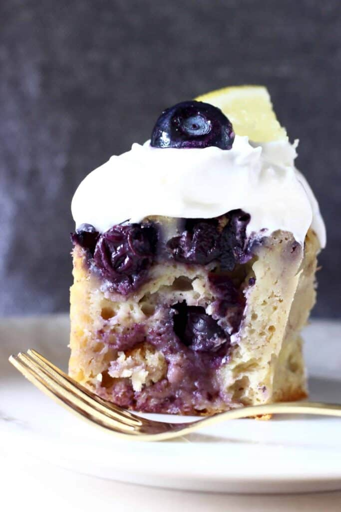 A slice of blueberry bundt cake topped with cream cheese frosting, a fresh blueberry and a lemon wedge on a white plate with a gold fork and a grey background