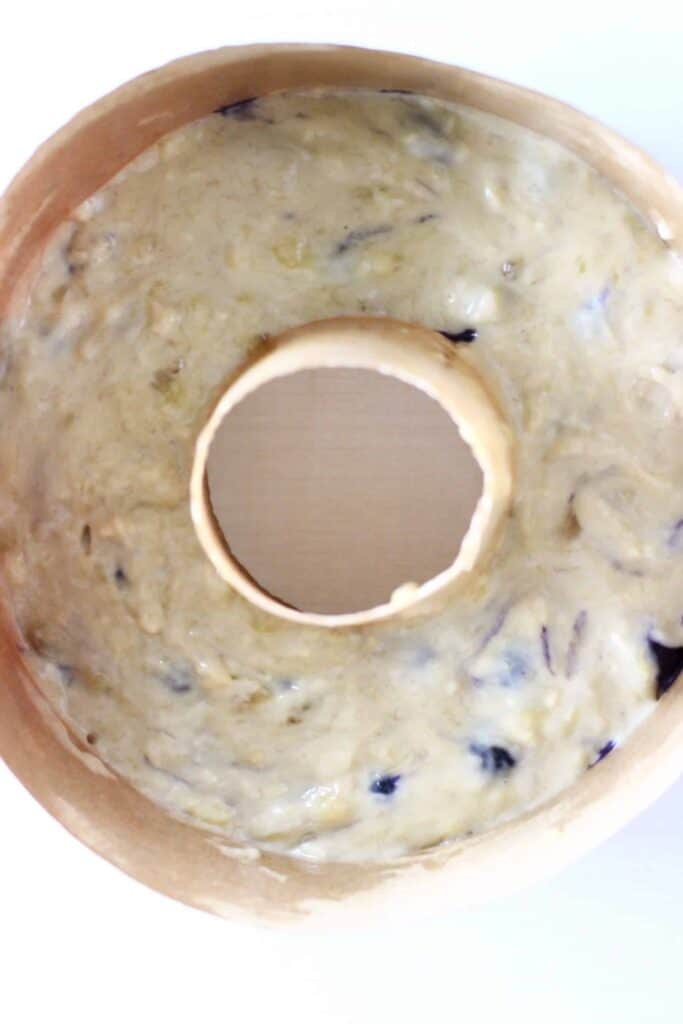 Cake batter dotted with blueberries in a bundt tin on a white background